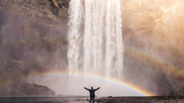 人生を変えた男性が滝の前で立つ